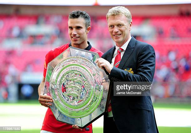 Robin van Persie of Manchester United and manager David Moyes pose with the trophy after victory in the FA Community Shield match between Manchester...