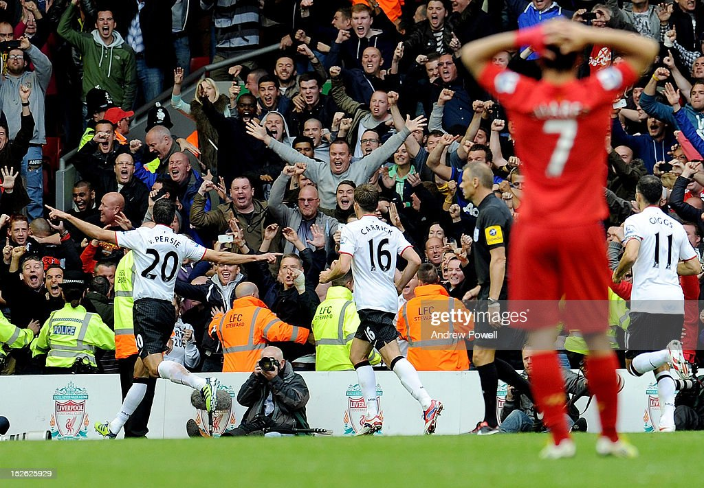 Robin Van Persie of Manchester United celebrates his penalty goal as Luis Surez of Liverpool has his head in his hands during the Barclays Premier League match between Liverpool and Manchester United at Anfield on September 23, 2012 in Liverpool, England.