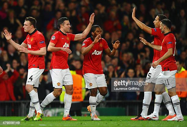 Robin van Persie of Manchester United celebrates scoring the second goal with his team-mates during the UEFA Champions League Round of 16 second...