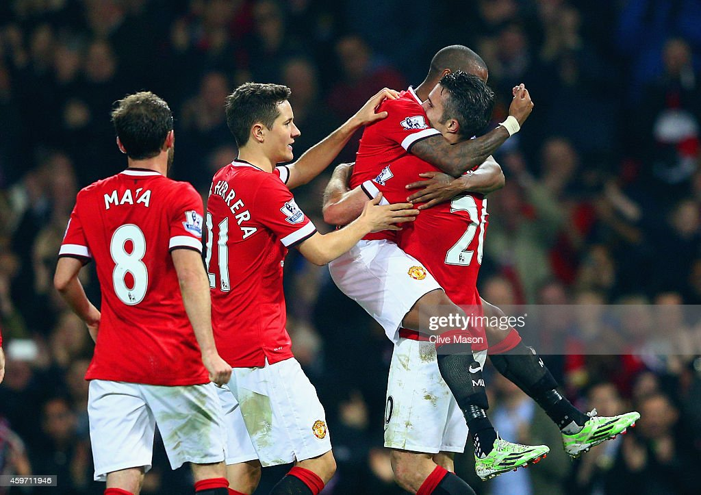 Robin van Persie of Manchester United (R) celebrates scoring their third goal with team mates during the Barclays Premier League match between Manchester United and Hull City at Old Trafford on November 29, 2014 in Manchester, England.