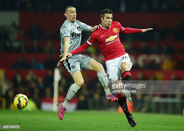 Robin van Persie of Manchester United is challenged by David Jones of Burnley during the Barclays Premier League match between Manchester United and...
