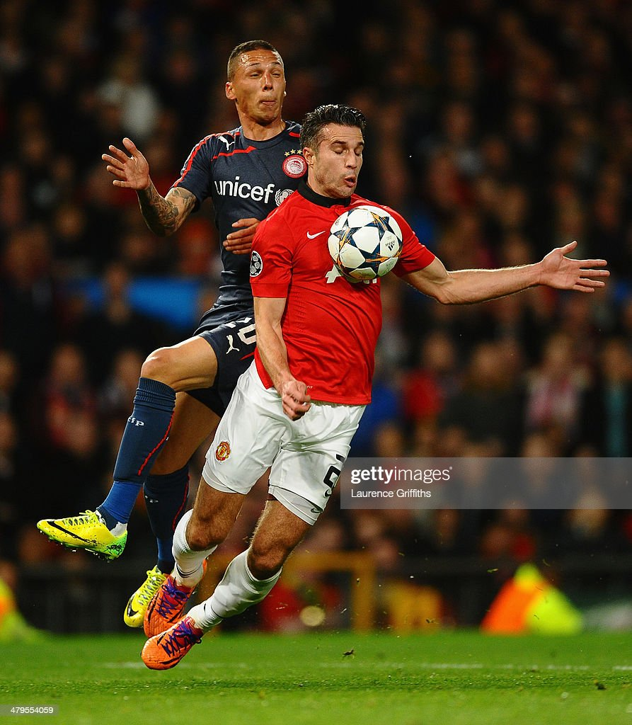 Robin van Persie of Manchester United is fouled in the penalty box by Jose Holebas of Olympiacos during the UEFA Champions League Round of 16 second round match between Manchester United and Olympiacos FC at Old Trafford on March 19, 2014 in Manchester, England.