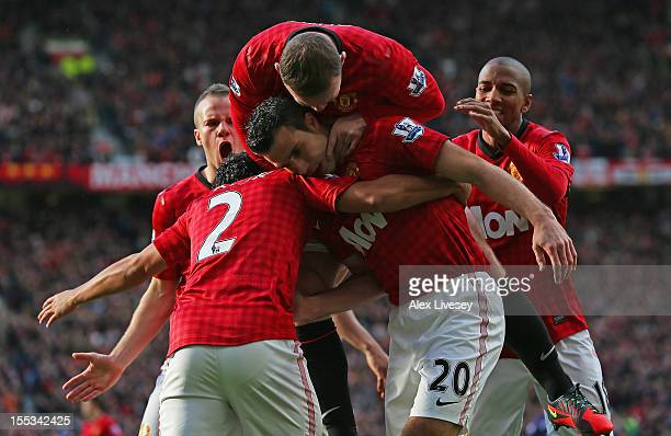 Robin van Persie of Manchester United is mobbed by his teammates after scoring the opening goal during the Barclays Premier League match between...