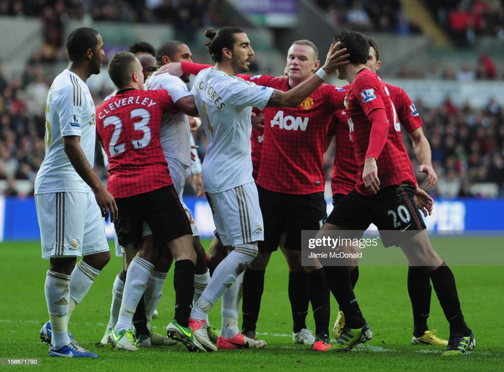 Robin Van Persie of Manchester United is pulled away from Ashley Williams of Swansea City during the Barclays Premier League match between Swansea City and Manchester United at the Liberty Stadium on December 23, 2012 in Swansea, Wales.