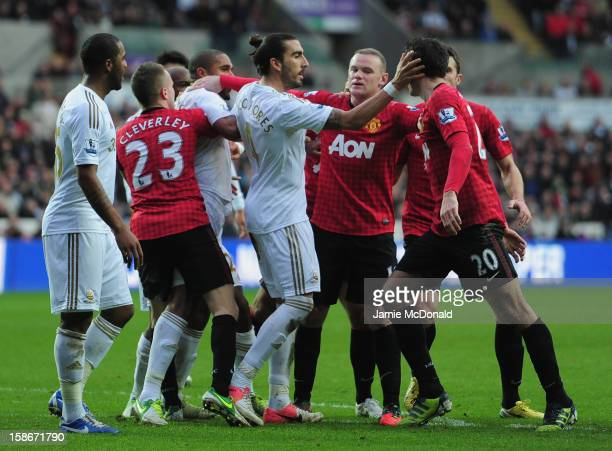 Robin Van Persie of Manchester United is pulled away from Ashley Williams of Swansea City during the Barclays Premier League match between Swansea...