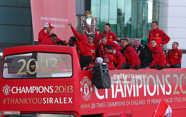 Robin Van Persie of Manchester United lifts the Premier League trophy as Sir Alex Ferguson and his team mates look on outside Old Trafford during the...
