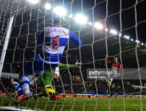 Robin van Persie of Manchester United sees his shot cross the line despite being cleared by Adrian Mariappa of Reading during the Barclays Premier...
