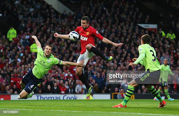 Robin van Persie of Manchester United shoots at goal under a challenge from Ron Vlaar of Aston Villa during the Barclays Premier League match between...