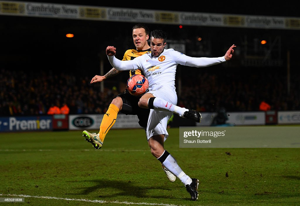 Robin van Persie of Manchester United shoots at goal under pressure from Josh Coulson of Cambridge United during the FA Cup Fourth Round match between Cambridge United and Manchester United at The R Costings Abbey Stadium on January 23, 2015 in Cambridge, England.