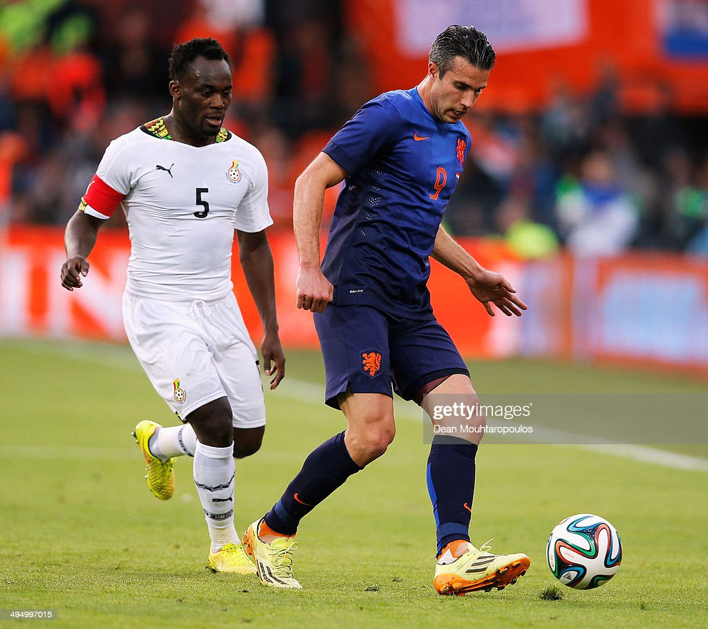 Robin Van Persie of Netherlands passes the ball in front of Michael Essien of Ghana during the International Friendly match between Netherlands and Ghana at De Kuip on May 31, 2014 in Rotterdam, Netherlands.