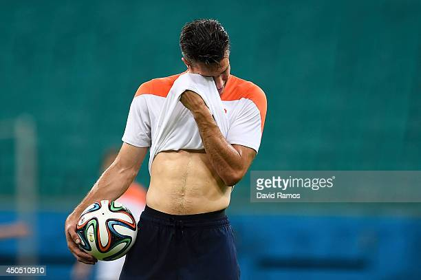 Robin Van Persie of Netherlands wipes his face during the Netherlands training session ahead the 2014 FIFA Word Cup Group B match between Spain and...