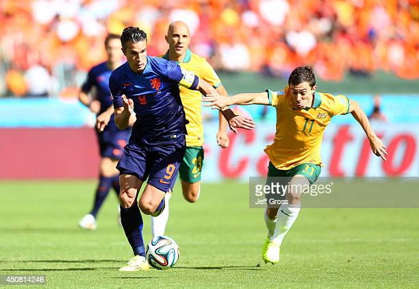 Robin van Persie of the Netherlands controls the ball against Tommy Oar of Australia during the 2014 FIFA World Cup Brazil Group B match between...