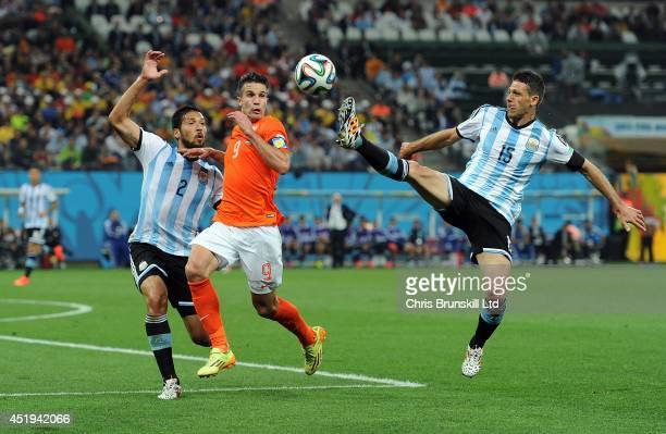 Robin Van Persie of the Netherlands in action with Ezequiel Garay and Martin Dimichelis of Argentina during the 2014 FIFA World Cup Brazil Semi Final...