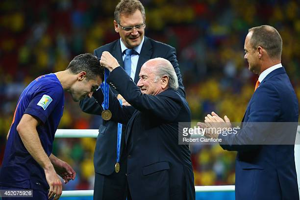 Robin van Persie of the Netherlands is presented with his medal by FIFA President Joseph S Blatter as KNVB Secretary General Bert van Oostveen looks...