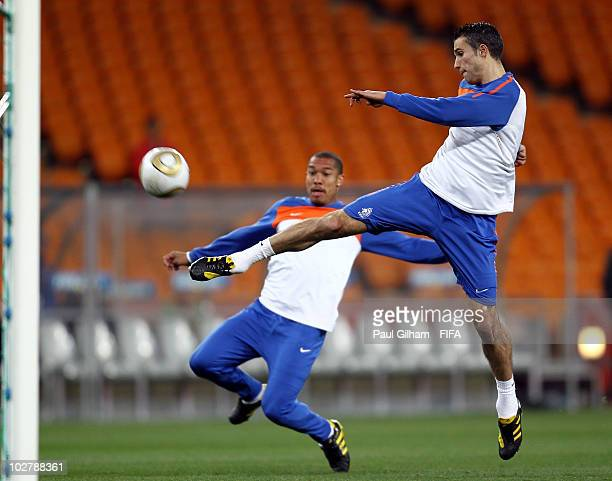 Robin Van Persie of the Netherlands shoots at goal watched by team mate Nigel De Jong during a Netherlands training session ahead of the 2010 FIFA...
