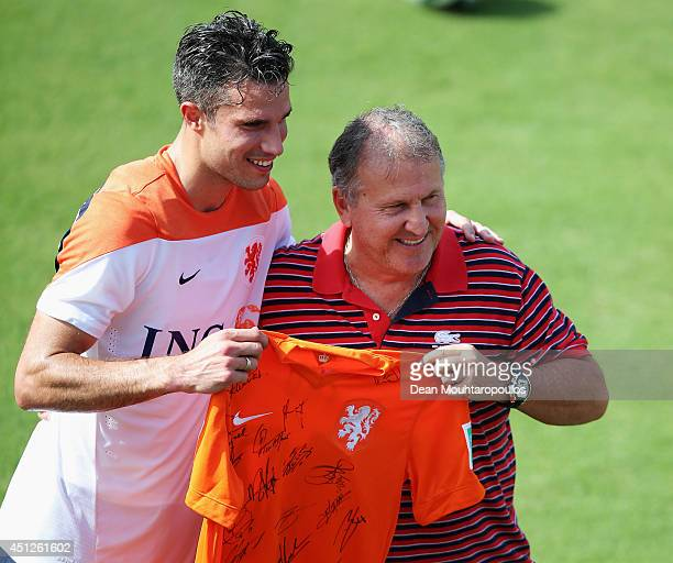Robin van Persie poses with Brazilian football Legend Zico as he is presented a signed Dutch shirt during the Netherlands training session at the...