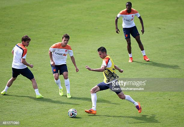 Robin van Persie shoots on goal in front of Paul Verhaegh and Joel Veltman during the Netherlands training session at the 2014 FIFA World Cup Brazil...