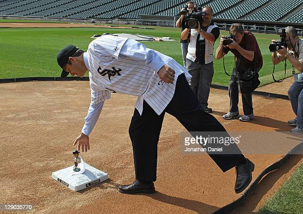 Robin Ventura, the new manager of the Chicago White Sox, reaches down to third base to pick up a bobble head doll left by the head grounds keeper...