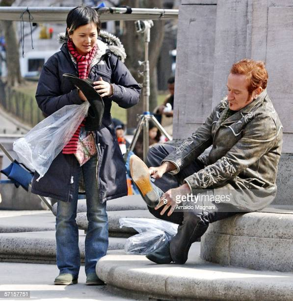 Robin Williams changes his shoes alongside an assistant during filming of their new movie 'August Rush' at Columbus Circle on March 22 2006 in New...