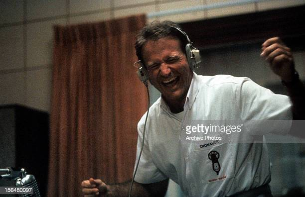 Robin Williams enjoying music through headset in a scene from the film 'Good Morning, Vietnam', 1987.