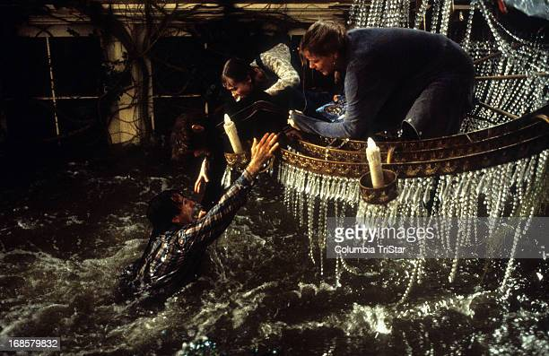Robin Williams hangs onto Bradley Pierce Kirsten Dunst and Bonnie Hunt in a scene from the film 'Jumanji' 1995