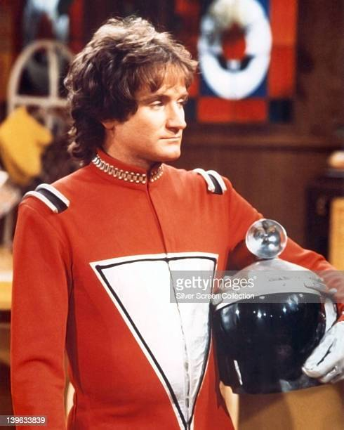 Robin Williams US actor and comedian in costume holding a helmet under his arm in a publicity portrait issued for the US television series 'Mork...