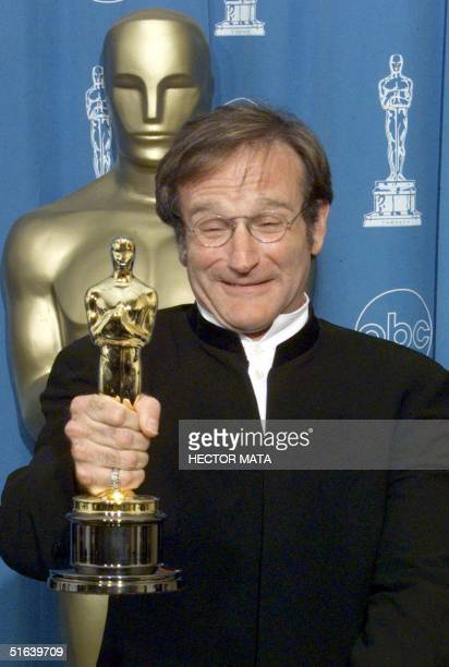 """Robin Williams, winner for Best Supporting Actors in """"Good Will Hunting"""", poses for photographers with the Oscar 23 March at the 70th Annual Academy..."""