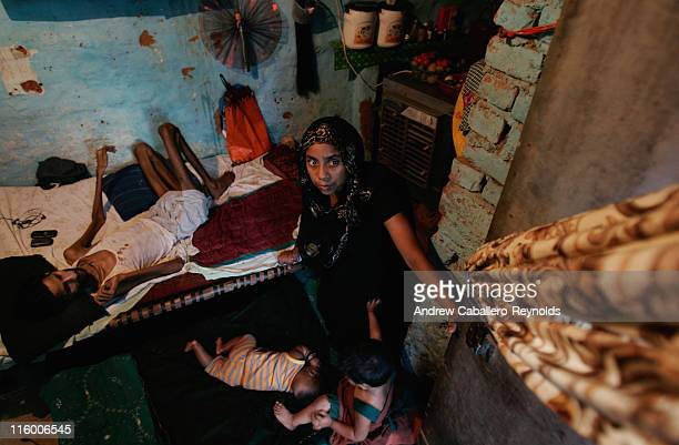 Robina wife of Resuti a tuberculosis patient being treated by operation ASHA looks out of their door as their children Ayan 3 months old and Farien 2...
