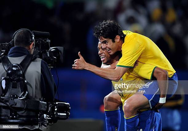 Robinho celebrates with his teammate Kaka in front of a television camera after Italy's Andre Dossena scores an own goal during the FIFA...