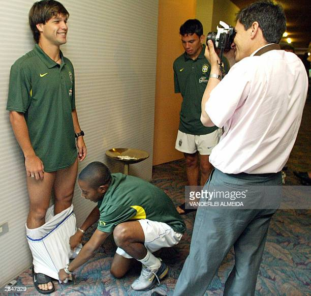 Robinho player of the Brazilian Under23 soccer team jokes with teammate Diego pulling down his shorts while a photographer takes his credential...