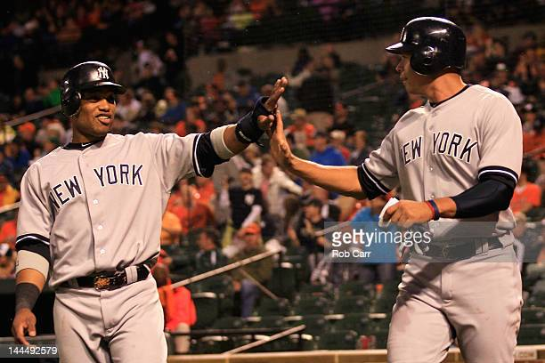 Robinson Cano and Alex Rodriguez of the New York Yankees celebrate after they both scored during the fourth inning against the Baltimore Orioles at...