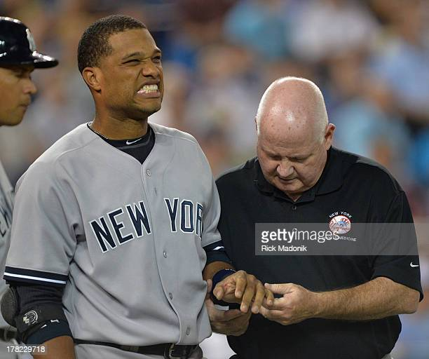 Robinson Cano grimaces as Athletic Trainer Steve Donohue checks out his finger after being hit by a pitch. Cano stayed in the game. Toronto Blue Jays...