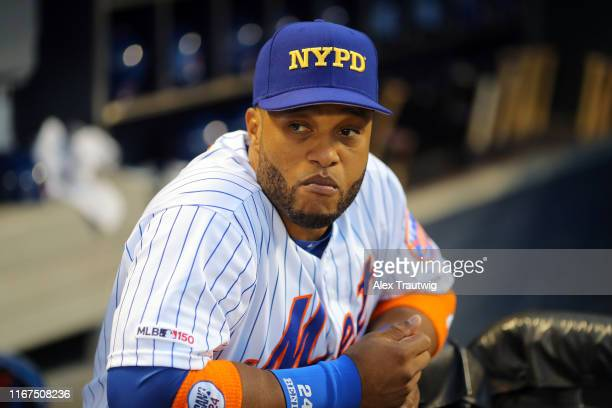 Robinson Cano of the New York Mets looks on from the dugout while wearing an NYPD hat before the game between the Arizona Diamondbacks and the New...