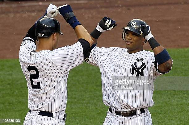 Robinson Cano of the New York Yankees celebrates his fifth inning grand slam home run against the Seattle Mariners with teammate Derek Jeter on...