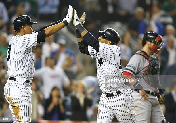 Robinson Cano of the New York Yankees celebrates his second home run of the night with Alex Rodriguez in the fifth inning against the Boston Red Sox...