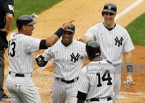 Robinson Cano of the New York Yankees celebrates his second inning grand slam against the Baltimore Orioles with teammates Alex Rodriguez Mark...