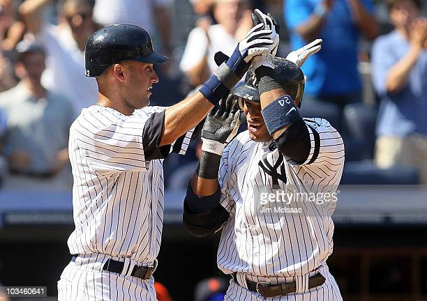 Robinson Cano of the New York Yankees celebrates his sixth inning two run home run against the Detroit Tigers with teammate Derek Jeter on August 19...