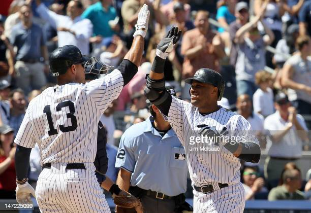Robinson Cano of the New York Yankees celebrates his sixth inning two run home run against the Cleveland Indians with teammate Alex Rodriguez at...