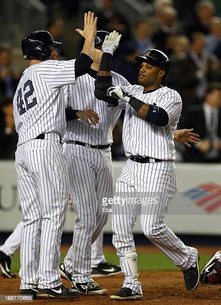 Robinson Cano of the New York Yankees celebrates his three run homer with teammates Lyle Overbay and Chris Stewart in the fourth inning against the...