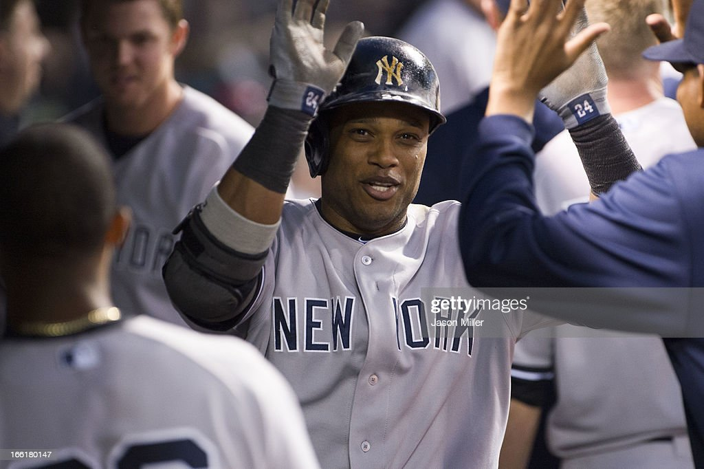 Robinson Cano #24 of the New York Yankees celebrates in the dugout after hitting a home run during the fourth inning against the Cleveland Indians at Progressive Field on April 9, 2013 in Cleveland, Ohio.