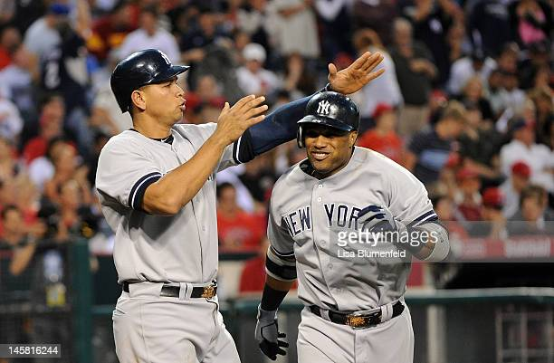 Robinson Cano of the New York Yankees celebrates with teammate Alex Rodriguez after hitting a tworun homerun in the third inning against the Los...