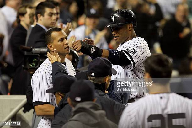 Robinson Cano of the New York Yankees celebrates with teammates including Alex Rodriguez after he scored on a RBI single by Jorge Posada in the...