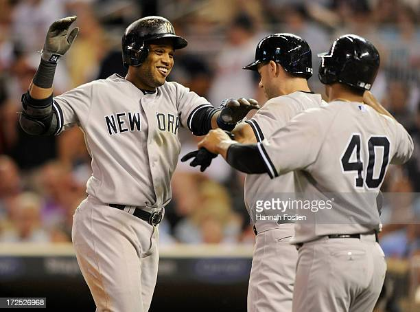 Robinson Cano of the New York Yankees celebrates with teammates Travis Hafner and Alberto Gonzalez after hitting a threerun home run against the...