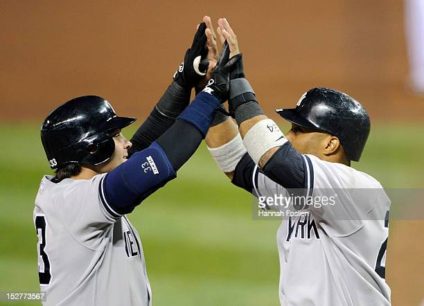Robinson Cano of the New York Yankees congratulates Nick Swisher on a two run home run against the Minnesota Twins during the fourth inning of the...