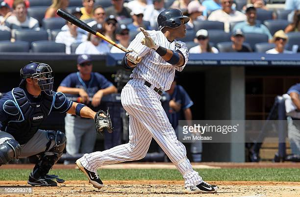 Robinson Cano of the New York Yankees follows through on a first inning two run triple against the Tampa Bay Rays on July 18 2010 at Yankee Stadium...