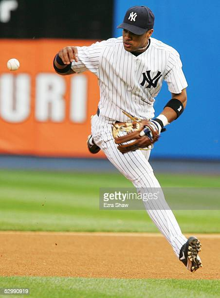 Robinson Cano of the New York Yankees fumbles the ball for an error on a hit by Johnny Damon of the Boston Red Sox in the first inning of the game at...