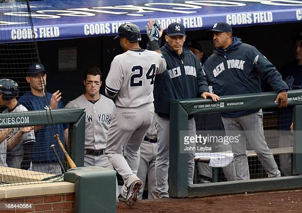 Robinson Cano of the New York Yankees high fives manager Joe Girardi after his home run in the fifth inning off of Adam Ottavino of the Colorado...