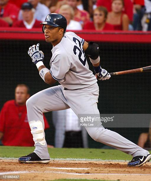 Robinson Cano of the New York Yankees hits a threerun double in his first postseason at bat in the first inning of 42 victory over the Los Angeles...