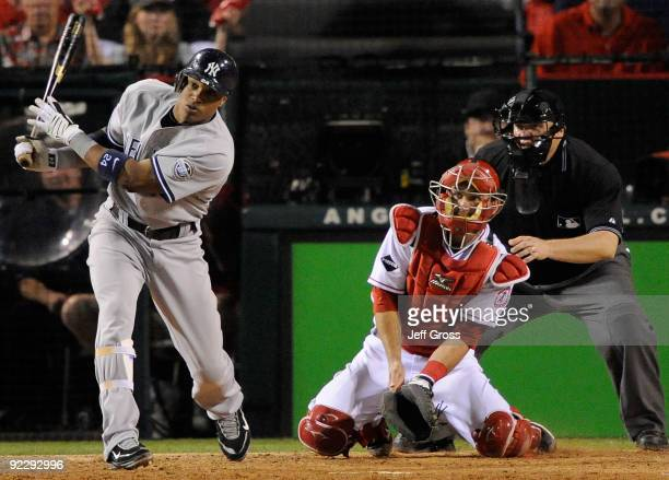 Robinson Cano of the New York Yankees hits a triple to right field during the seventh inning in Game Five of the ALCS against the Los Angeles Angels...