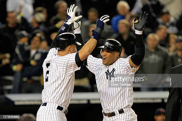 Robinson Cano of the New York Yankees is congratulated by Derek Jeter after hitting a grand slam home run in the sixth inning of Game One of the...